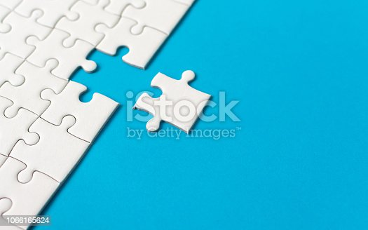 White jigsaw puzzle on blue background. Team business success partnership or teamwork.