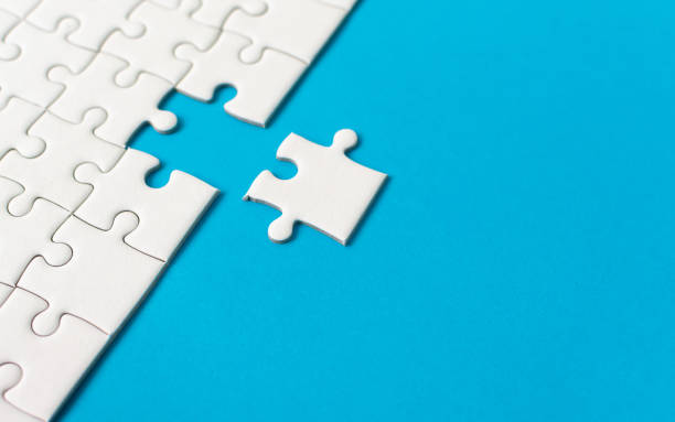 White jigsaw puzzle on blue background. Team business success partnership or teamwork. stock photo