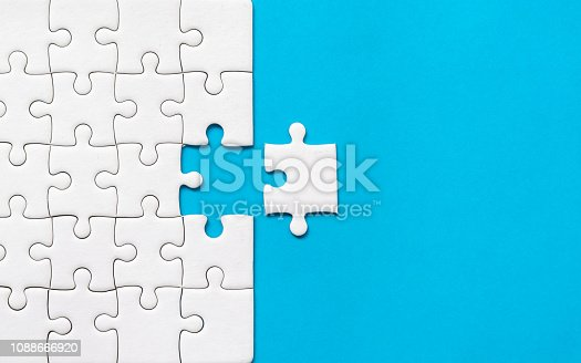 istock White jigsaw puzzle on blue background. Team business success partnership or teamwork. 1088666920