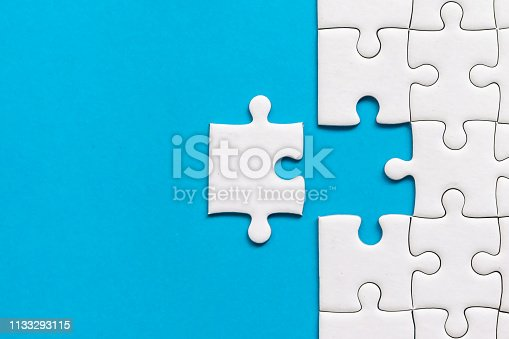 istock White jigsaw puzzle on blue background. Team business success partnership or teamwork 1133293115