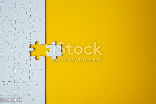 White jigsaw puzzle on yellow background. Team business success partnership or teamwork.