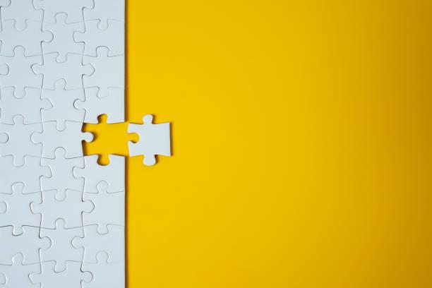 weißes puzzle auf gelbem hintergrund. team-business-erfolgspartnerschaft oder teamwork. - berufliche partnerschaft stock-fotos und bilder