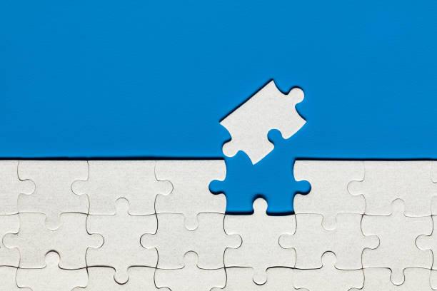 Weiße Puzzleteile. Füllen Sie Teile des Puzzles. Vervollständigen Sie das Puzzle mit den fehlenden Teilen. Fragment eines gefalteten weißen Puzzles. – Foto