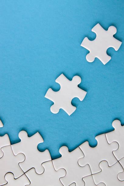 weiße puzzlestücke auf blauem hintergrund - puzzleteil stock-fotos und bilder