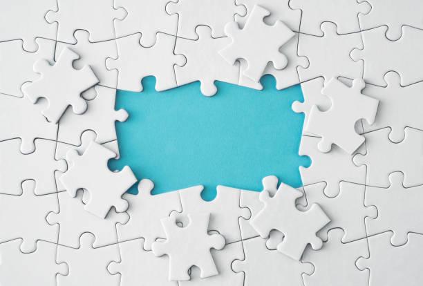 witte puzzelstukjes op blauwe achtergrond - raadsel stockfoto's en -beelden