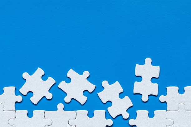 Weißes Puzzle. Weiße Puzzleteile auf farbigem Hintergrund. Unvollendete weiße Puzzleteile auf farbigem Hintergrund. – Foto