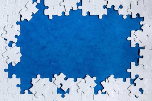 Weiße Sitte Puzzle. Weiße Puzzleteile auf Farbhintergrund. Unvollendete weiße Puzzleteile auf Farbhintergrund. – Foto