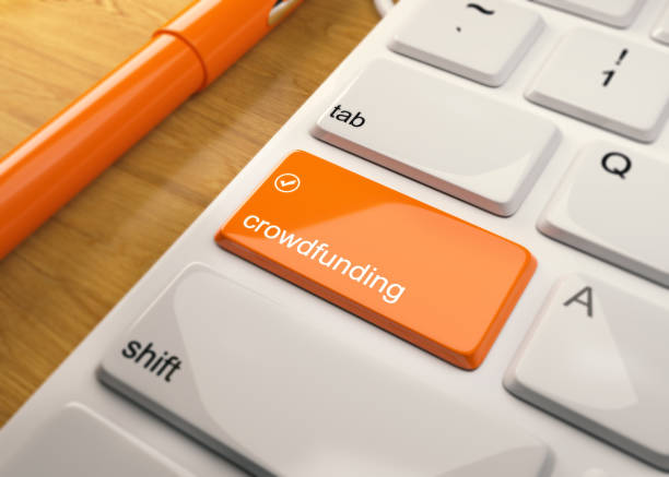 White Keyboard With Crowdfunding Button On Wood Table stock photo