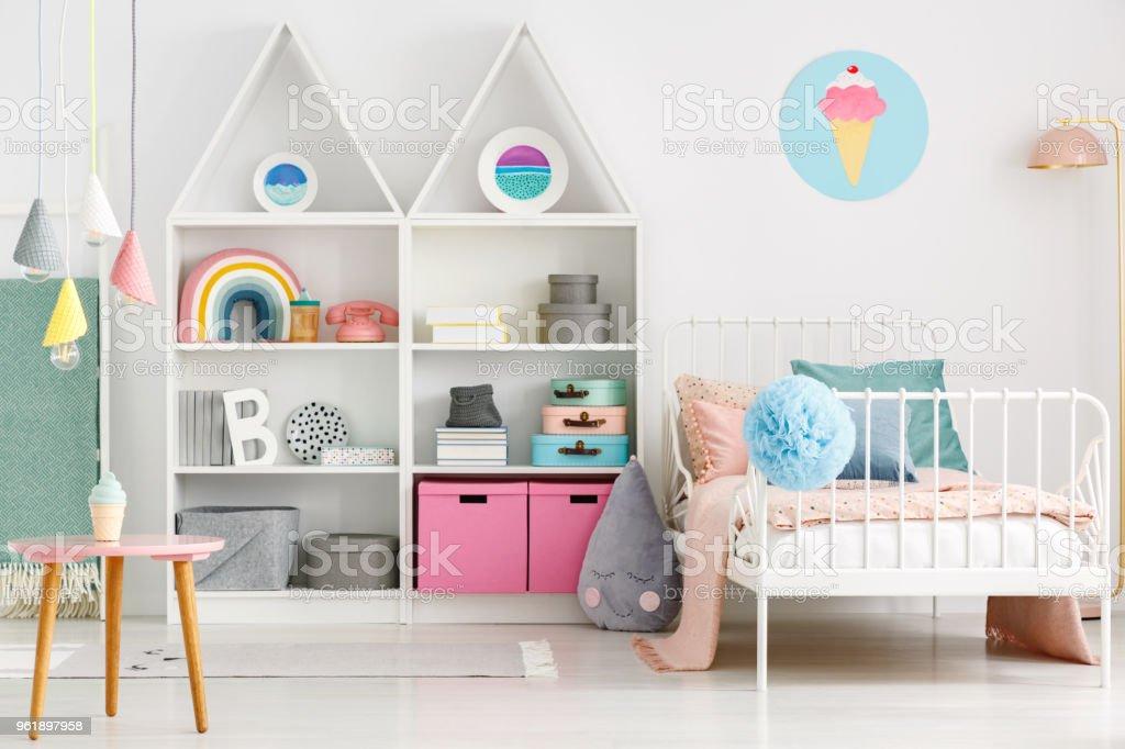 Branco interior de quarto infantil com uma cama de solteiro, um arco-íris na prateleira, pompom e sorvete pôster na parede - foto de acervo