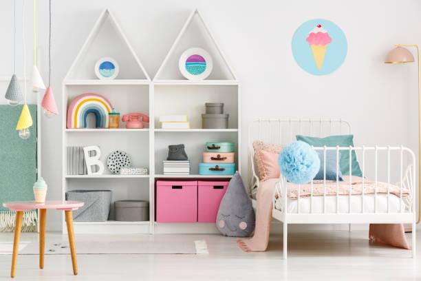 weiße kinder innenraum mit einem einzelbett, regenbogen auf dem regal, bommel und eis-poster an der wand - kinderzimmer tischleuchten stock-fotos und bilder