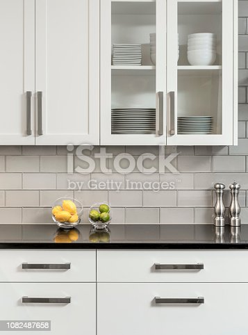 Detail of white kitchen cabinets with black counter top