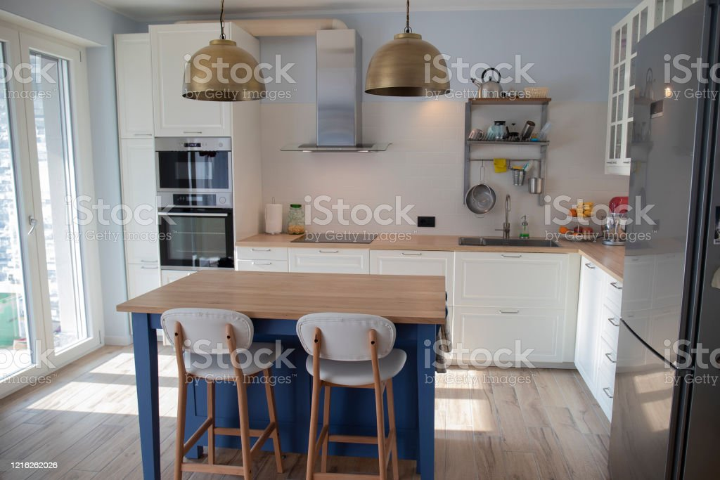 White Kitchen With Blue Island And Wooden Floor Stock Photo Download Image Now Istock