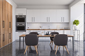 Interior of stylish kitchen with white walls, tiled floor, white cabinets and dining table. 3d rendering
