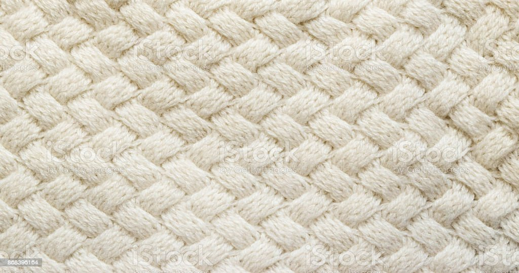 White knitted carpet closeup. Textile texture off white background. Detailed warm yarn background. Knit cashmere beige wool. Natural woolen fabric, sweater fragment. stock photo