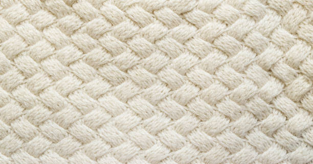 white knitted carpet closeup. textile texture off white background. detailed warm yarn background. knit cashmere beige wool. natural woolen fabric, sweater fragment. - wool stock photos and pictures