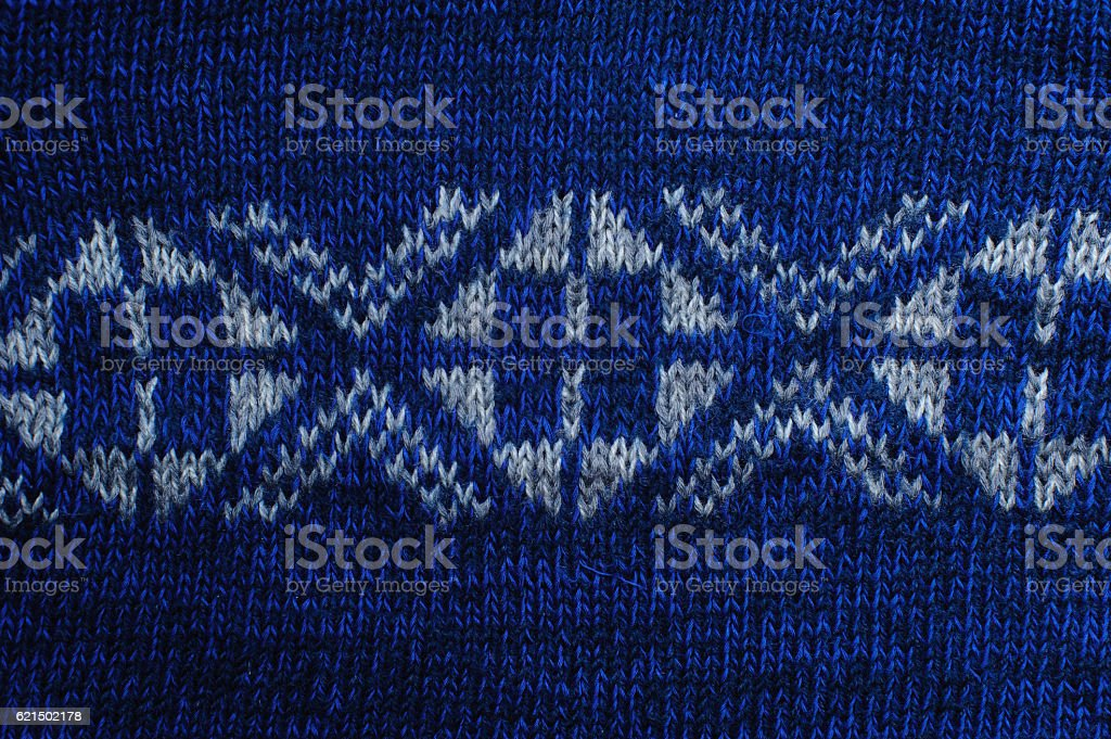 White knitted ornament on blue woolen texture foto stock royalty-free