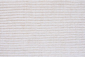 White knitted woolen fabric texture. Knitted white background with horizontal direction. Focusing in the center of the frame