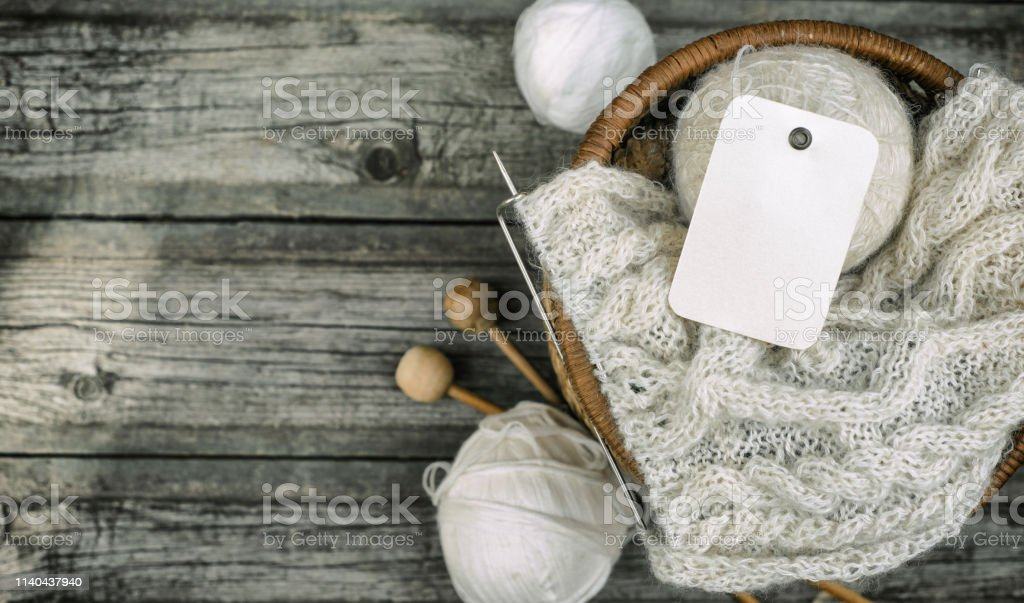White label on wool threads roll to basket with knitting and knitting...