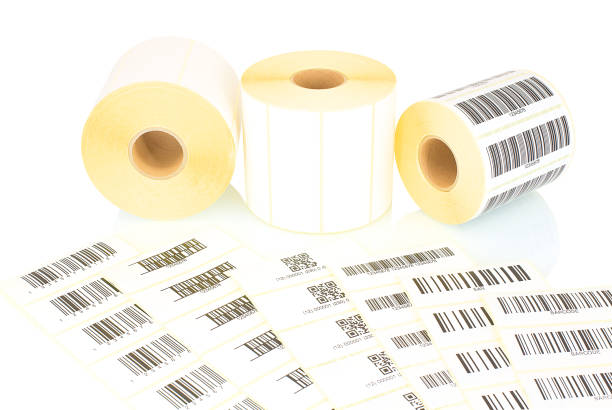 White label rolls and printed barcodes isolated on white background with shadow reflection. White reels of labels for printers. Labels for direct thermal or thermal transfer printing. Barcode samples. White label rolls and printed barcodes isolated on white background with shadow reflection. White reels of labels for printers. Labels for direct thermal or thermal transfer printing. Barcode samples. labeling stock pictures, royalty-free photos & images