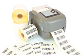 istock White label rolls, printed barcodes and printer isolated on white background with shadow reflection. White reels of labels with printer. Labels for direct thermal or thermal transfer printing. 950305672