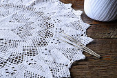 A close up image of a white crochet lace doily, three crochet hooks, and ball of yarn.