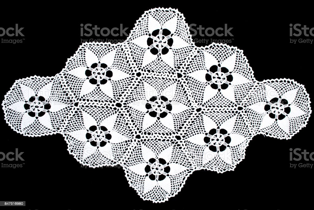 White lace tablecloth isolated on black background, floral pattern stock photo