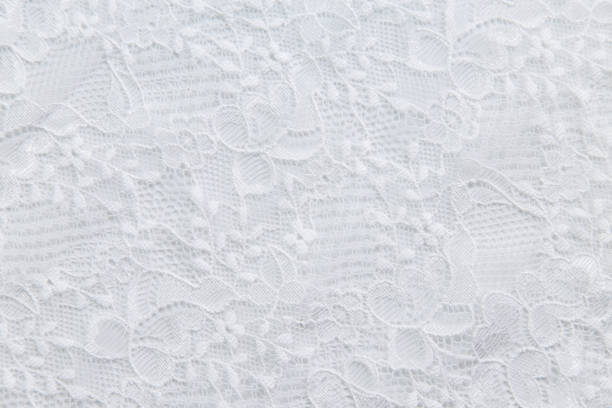 White lace with small flowers on the white background White lace with small flowers on the white background. lace textile stock pictures, royalty-free photos & images