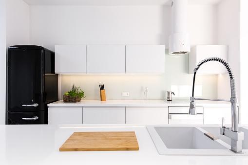 White, lacquer kitchen and black retro fridge