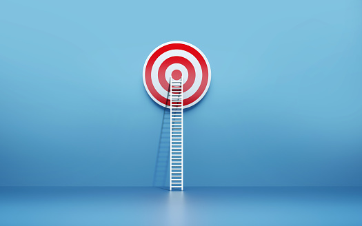 White ladder leaning on a red target on blue wall. Horizontal composition with copy space.