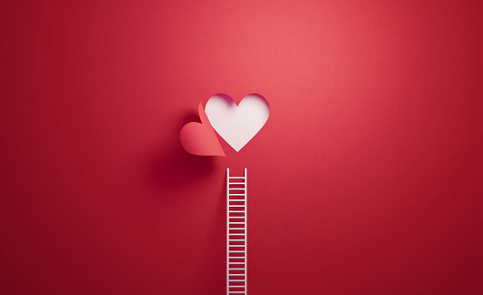 White ladder leaning on red wall with cut out heart shape. Horizontal composition with copy space.