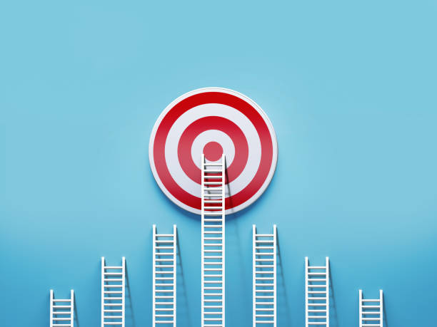 White Ladders Leaning on A Target on Blue Wall White ladders leaning on a red target on blue wall. Horizontal composition with copy space. wishing stock pictures, royalty-free photos & images