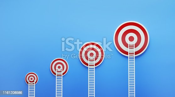 istock White Ladders Leaning on Red Targets on Blue Wall 1161208586