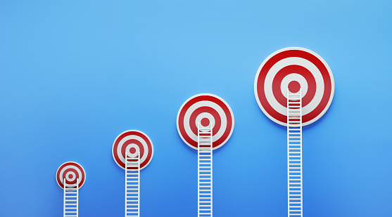 White ladders leaning on red targets on blue wall. The targets form a graph. Horizontal composition with copy space. Growth concept.