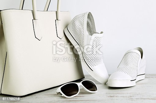 istock White ladies handbag, shoes and sun glasses on  light background 611765218