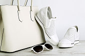 White ladies handbag, shoes and sun glasses on  light background