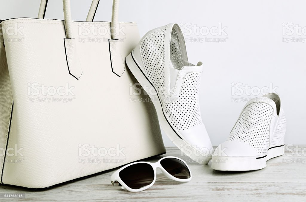 White ladies handbag, shoes and sun glasses on  light background stock photo