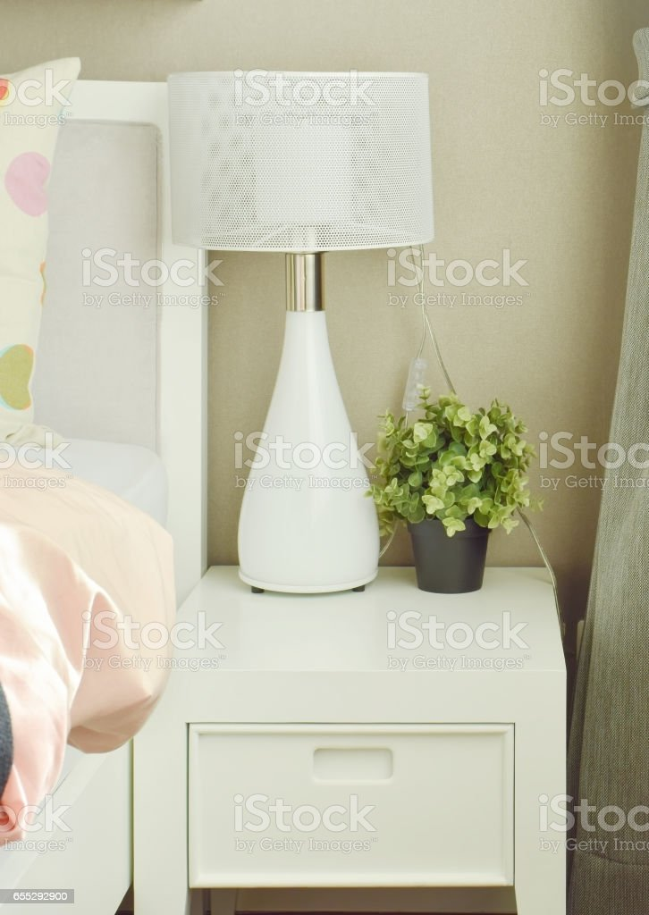 White Lamp And Flower Pot On Bedside Table Next To Bed Stock Photo