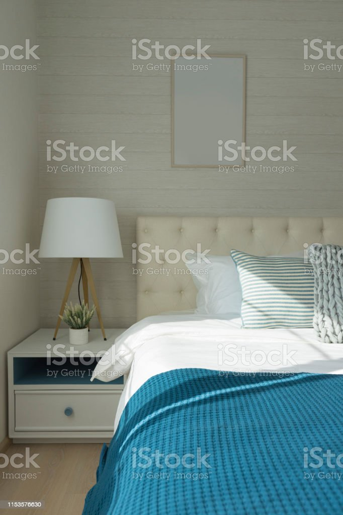 White lamp next to king size bed with navy blue bedding.