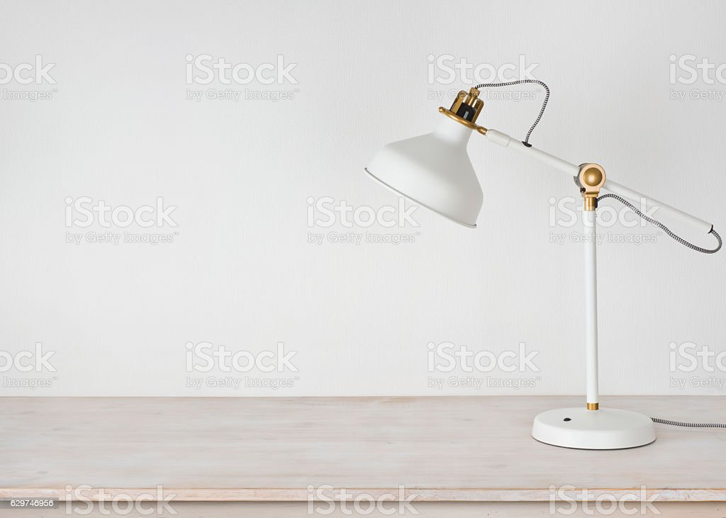 White lamp on wooden desk in room with copy space stock photo