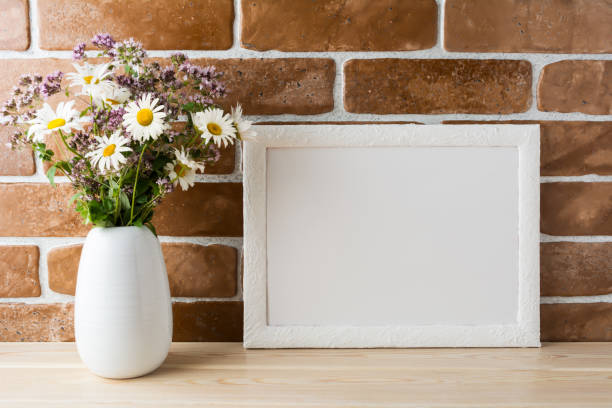 White landscape frame mockup with wildflowers bouquet in styled vase stock photo