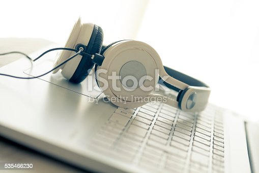 White laptop and headphenes on table, a concept for transcription, music services and others.