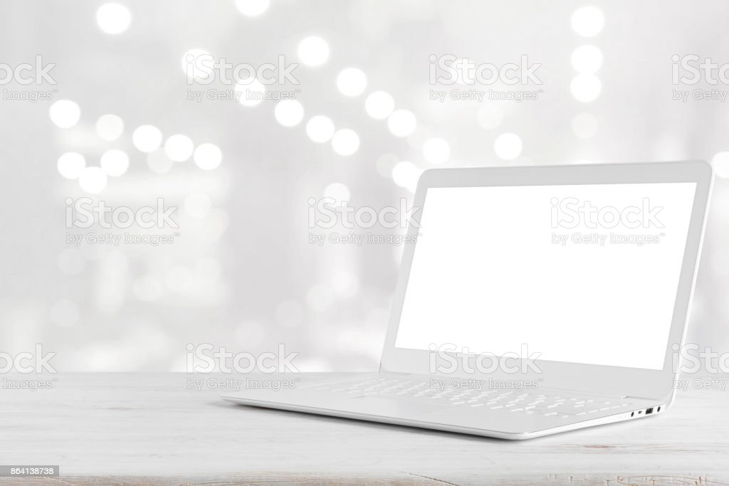 White laptop computer on wooden table over abstract lights background royalty-free stock photo