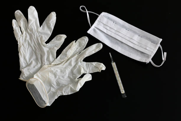 White latex gloves, thermometer and medical mask stock photo