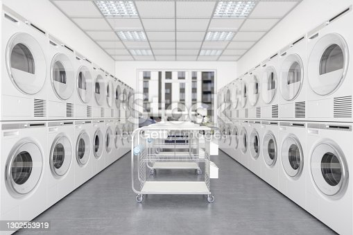 White Laundry Machines And Dryers In A Row In Laundromat With Wheeled Laundry Baskets.