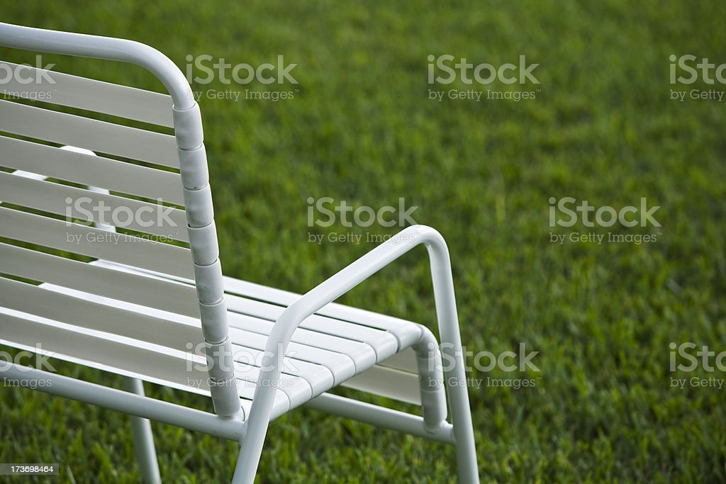 White Lawn Chair on Green Yard Grass royalty-free stock photo