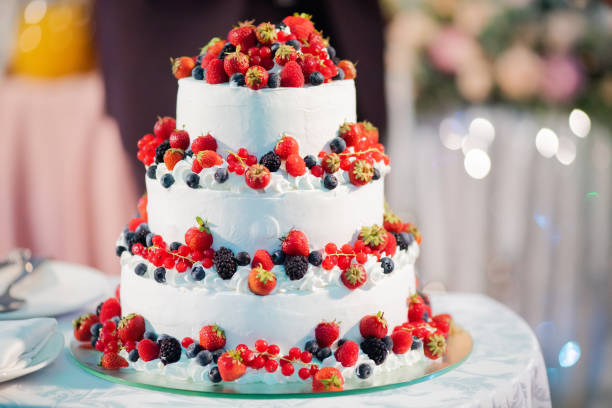 white layer cake decorated with berries, served with fireworks. stock photo
