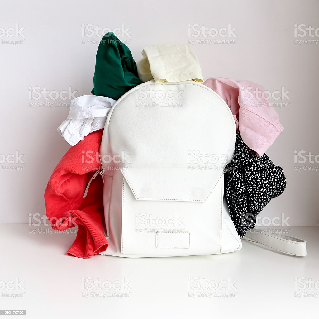 White leather bag (daypack) with clothing, shoes and sunglasses stock photo
