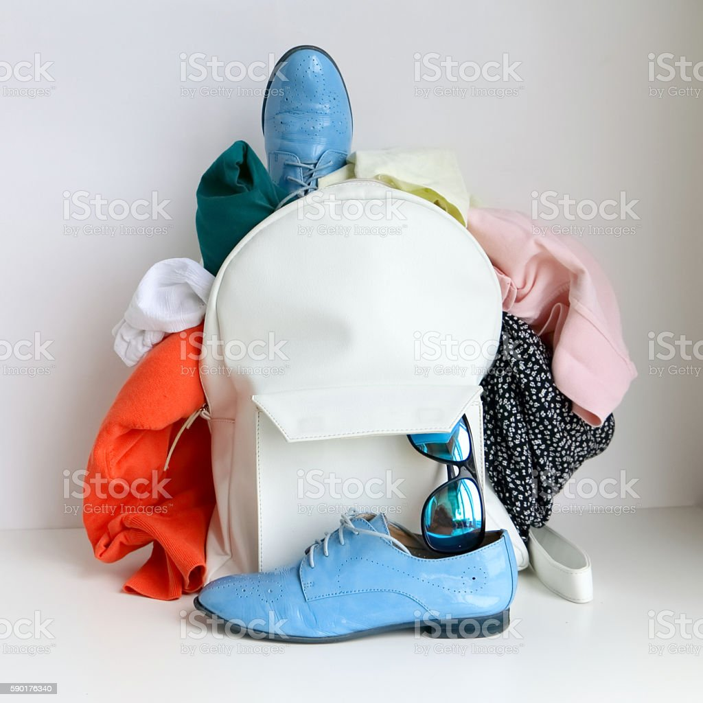 White leather bag (daypack) with clothing, shoes stock photo