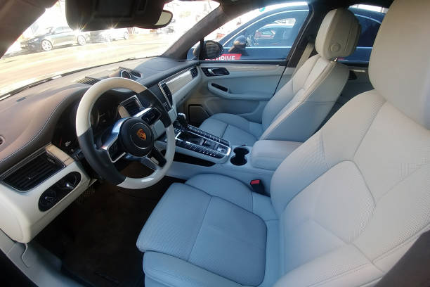 White leather interior of an premium SUV Porsche Macan parked on the street. Package trim car of white oak and wooden heated steering wheel. stock photo