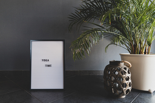 """White letterboard. Grey wall. Green plant. With the inscription """"YOGA TIME""""."""